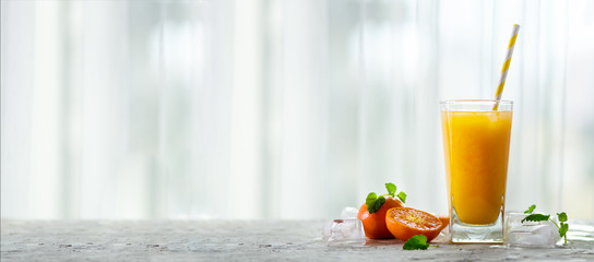 Fresh tangerine juice in glass on white concrete background. Orange fruits with ice, mint. Cold beverage for hot summer day. Copyspace. Banner.
