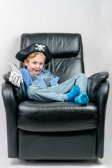 Cute and smiling five year old boy dressed up in a pirate and police officer costume sit and laze in an black leather armchair.