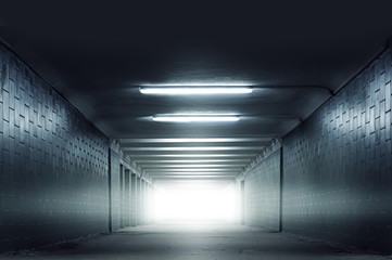 Dark blue urban subway tunnel with light in the end without people photo