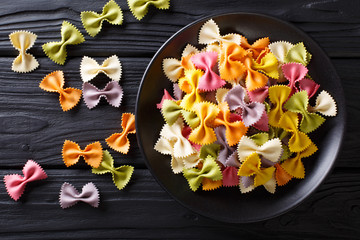 Beautiful Italian uncooked colored farfalle pasta close-up. horizontal top view