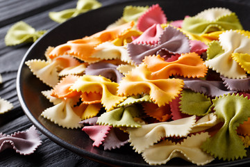 Beautiful Italian uncooked colored farfalle pasta close-up. horizontal