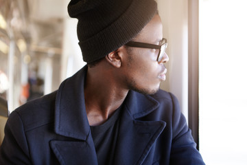 Profile of young African American tourist dressed in trendy clothing sitting in bus and looking through window watching people and surroundings outside while traveling alone in foreign country