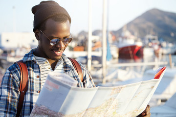 Side view of dark-skinned tourist with backpack in trendy hat and sunglasses examining directions using his paper road map on blurred background of yacht park or club in picturesque resort town