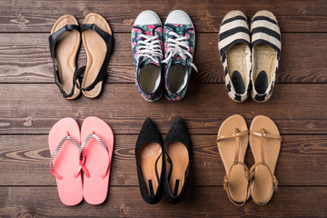 Collection of women's shoes on wooden background