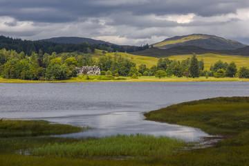 House on scottish lake after a thunderstorm, typical scottish landscape, Scotland