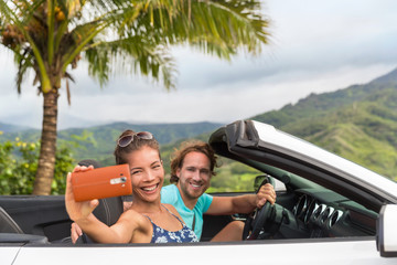 Car holiday selfie. Couple having fun on summer vacation road trip taking smartphone pictures during travel. Multiracial young people driving convertible.