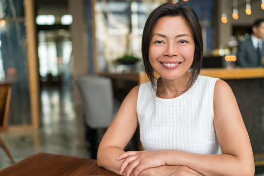 Happy elegant Asian middle-aged businesswoman smiling portrait. Beautiful mature Chinese business woman in fancy restaurant, China.