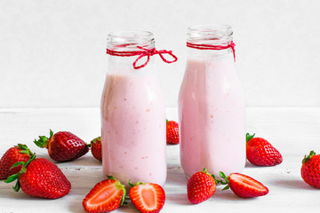 Strawberry smoothie or milkshake in a bottle with fresh berries