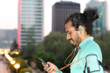 Smiling young ethnic man with smartphone and earphones