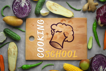 Wooden cutting board and vegetables on color background
