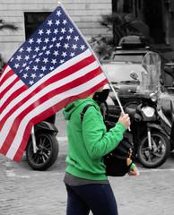 Ragazza porta in spalla una bandiera americana per le strade di Roma. Le stelle e strisce del vessillo americano sventolano al vento capitolino.