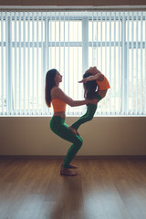Healthy morning stretching - woman with daughter doing gymnastic exercise at home, yoga exercise