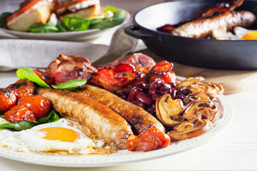 Delicious full English breakfast with fried egg, bacon, sausage, tomatoes, beans and mushrooms.  Traditional english breakfast on white wooden background, close-up.