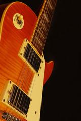 Papiers peints Rouge, noir, blanc Vintage electric jazz guitar closeup on the black background. Shallow depth of field.