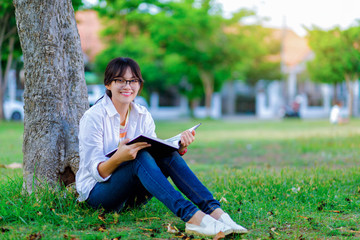 smiling asian girl reading book under tree in public park and look at camera