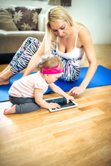Toddler girl using tablet with help of her mother