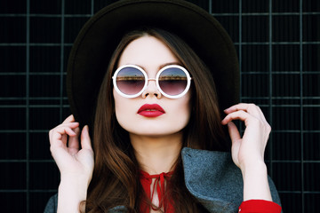 Outdoor close up portrait of young beautiful woman with long hair, red lips, wearing stylish wide-brimmed hat, round white sunglasses posing on street. Model looking at camera. Female fashion concept