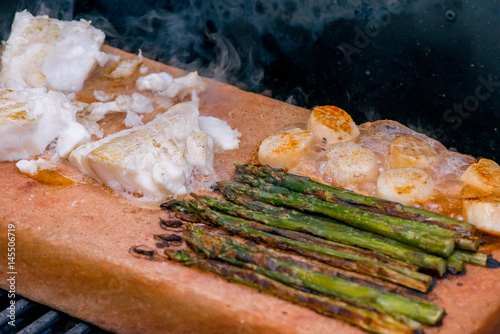 Fish asparagus and scallops cooking on a salt block with for Cooking fish on a salt block