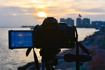 Photography camera while taking beautiful cloudy sunset scene.