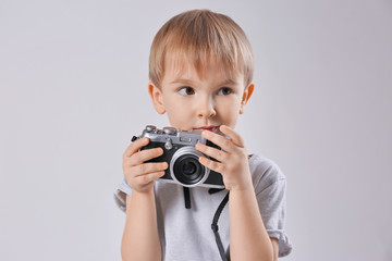 Cute boy with film camera on light background