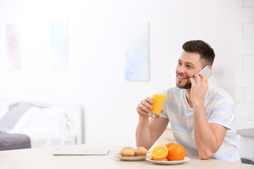 Handsome man holding glass of juice and talking on phone at home