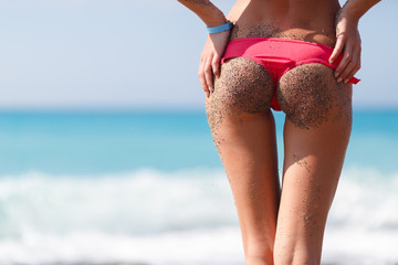 Sexy back of a girl in a pink bikini and the sand from the beach against the sea, swimsuit in small pebbles, pleasure, tourism.