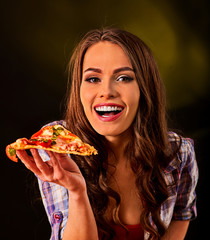 Woman eating slice of Italian pizza . Student consume fast food. Healthy eating and diet concept on black background.