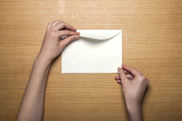 woman hand hold a white envelope on the wood table(background)
