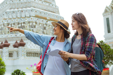 Two beautiful women is looking up the map at Wat Po, Thailand