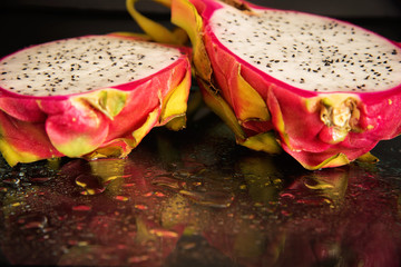Fresh dragon fruit cut in half on a on black background.