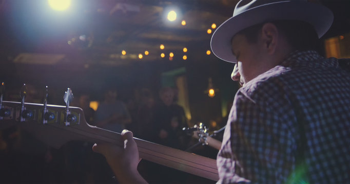 Musician - guitarist in hat plays guitar in night club, rear view