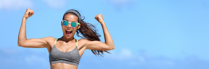 Strong fitness woman banner crop with copyspace on sky. Girl in sunglasses showing off muscular arms flexing biceps for fun on beach. Weight loss success concept.