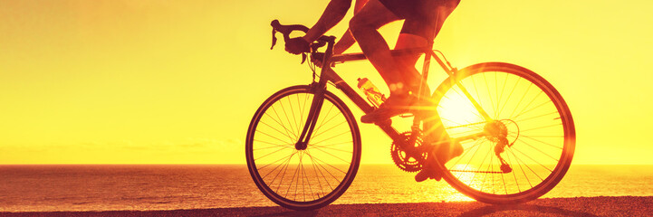 Foto auf AluDibond Radsport Cyclist biking on road bike sunset banner. Active healthy sports lifestyle athlete cycling.