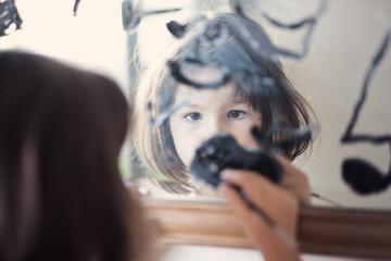 Child draws on the mirror