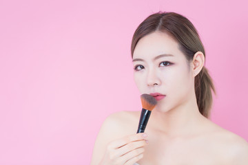 Portrait of young beautiful caucasian asian woman applying cosmetic brush powder. cosmetology, skincare, cleaning face, plastic surgery and SPA therapy concept on pink background