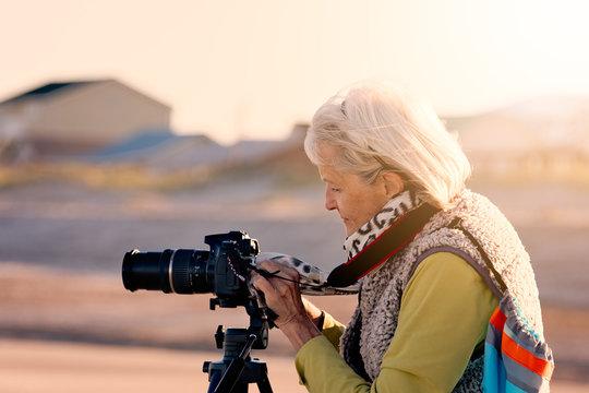 Senior woman doing photography on a beach in Florida