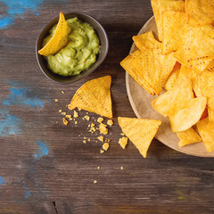 Snack for a party, chips with a tortilla, nachos with sauces: guacamole. Mexican food. Dark background. Top view. Copy space