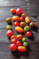 Colorful ripe tomatoes. Delicious vegetarian food. Dark background. top view