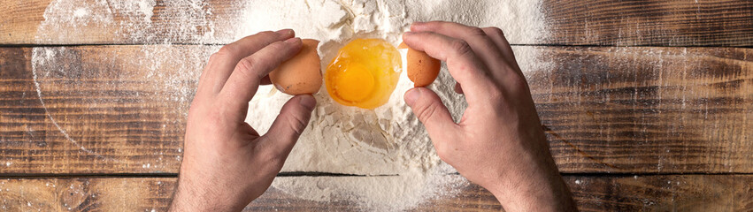 Male hands beat the egg yolk into the flour