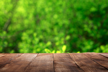 Empty wooden table with blur green leaves bokeh background