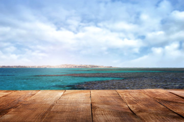Wooden table in the background of the ocean and sky