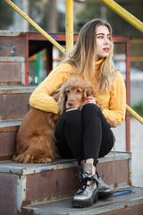 Portrait. A beautiful sexy girl, blonde, a young woman, looking like Jennifer Aniston sitting with a Cocker Spaniel dog, on a rusty metal stairway