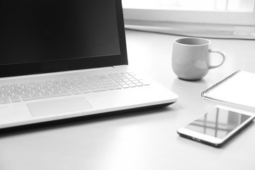 Business Notebook computer with smart phone , notebook paper for note message and a cup of coffee on wood desk background ( soft focus black and white photo )