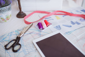 Close-up of a table equipped with working things for sewing, indoors