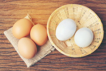 Eggs in basket with old beautiful wooden background.
