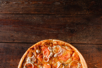 Delicious fresh baked yummy pizza with ham, cheese, tomato and onion served on rustic wooden table, flat lay. Dark background with free space for text.