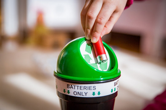 Little girl putting used batteries into recycling box at home. Child in the house room separating waste. Batteries Only.