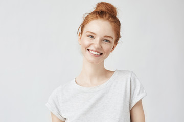 Headshot Portrait of happy ginger girl with freckles smiling looking at camera. White background.