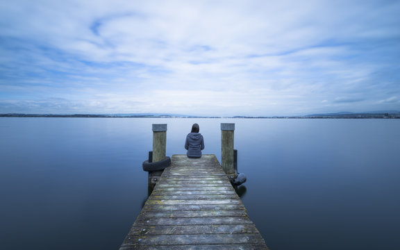 Overcast. Self reflection in magical world of fantasy. One woman sits on a wooden pier. Cloudy above the lake. Long exposure.