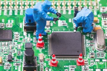 Miniature computer engineers working on a computer circuit board